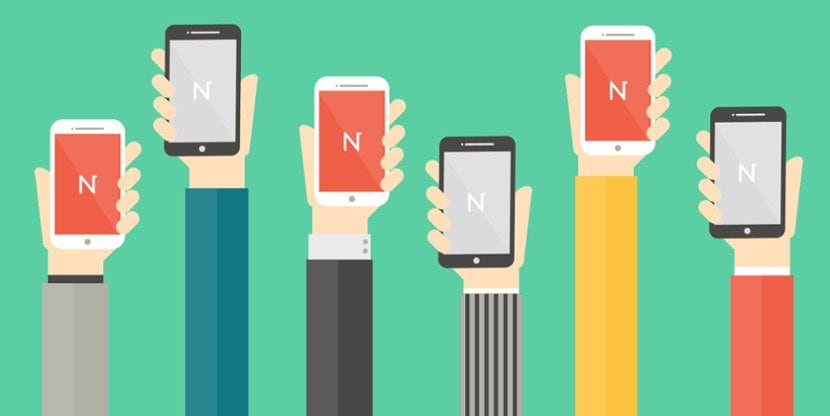 cartoon of hands raised in the air holding mobile phones with the letter N in the middle of the screen