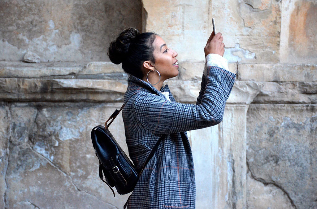 Female holding phone in the air taking a photo